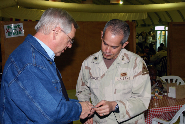 US Congressman the honorable Kurt Weldon, Republican for Pennslyvania (PA), Vice Chairman of the House Armed Services Committee, talks with US Army (USA) Lieutenant Colonel (LCOL) Alfonso Franqui of the 1ST Armored Division, during a Congressional visit to the Bob Hope Dining Facility, Baghdad International Airport (BIA), Iraq (IRQ), during Operation IRAQI FREEDOM