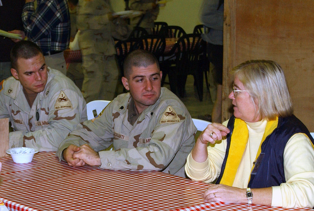 US Congresswoman the honorable Candice S. Miller, right, Republican for Michigan (MI), a member of the House Armed Services Committee, talks with US Army (USA) Private First Class (PFC) Nicolas Luchenbill, left, with the 141st Signal Battalion (SB), Company B and SPECIALIST (SPC) Luigi Magnanti, A Company, 1-13 Armored Regiment over dinner at the Bob Hope Dining Facility, at Baghdad International Airport (BIA), Iraq (IRQ), during Operation IRAQI FREEDOM