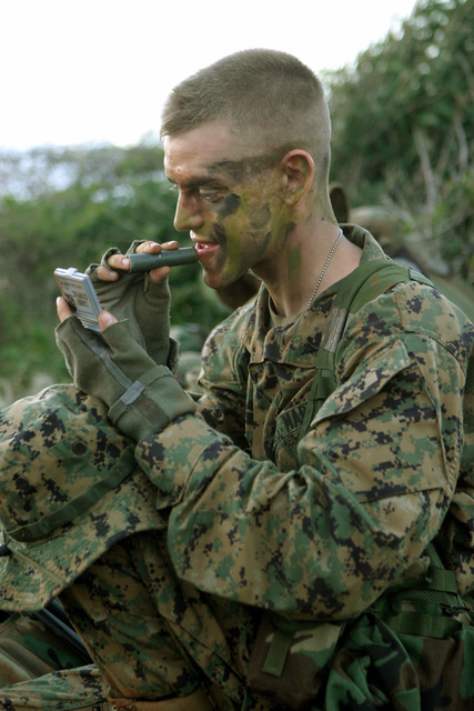 US Marine Corps Reserve (USMCR) Lance Corporal (LCPL) Justin McCrory, Rifleman, Kilo Company (K CO), 3rd Battalion, 25th Marines (3/25), reapplies camouflage face paint in the early morning light during a field exercise in Curacao, Netherlands Antilles. The Dutch Bilateral Training is an annual cooperative exchange between the US Marine Corps Reserves (USMCR) and the Royal Netherlands Marine Corps where differing ideas and tactics are discussed and tested in a field environment