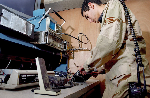 US Air Force (USAF) SENIOR AIRMAN (SRA) Mikhail Testa of the 447th Expeditionary Communications Squadron (ECS) replaces a Motorla Land Mobile Radio (LMR) base station at Baghdad International Airport (BIA), Iraq (IRQ), in support of Operation IRAQI FREEDOM