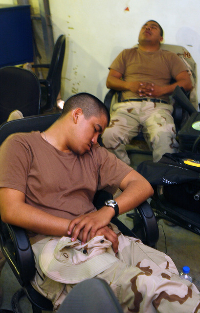 US Army (USA) Soldiers attached to the 328th Personnel Service Battallion (PSB) sleep while they wait for their flights in the Passenger Terminal (PAX) at Baghdad International Airport (BIA), Iraq (IRQ), in support of Operation IRAQI FREEDOM