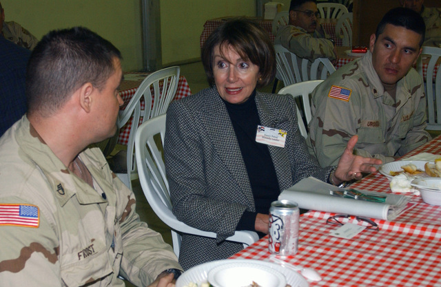US House Representative Nancy Pelosi Democrat of California (CA), visits with US Army (USA) STAFF Sergeant (SSGT) Andy Frost and SPECIALIST (SPC) Caesar Urquiza from CA, in the Bob Hope Dining Facility near Baghdad International Airport (BIA), Iraq (IRQ), part of a Congressional Delegation during Operation IRAQI FREEDOM