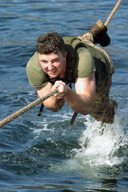 US Marine Corps Reserve (USMCR) Lance Corporal (LCPL) Elliot Danish, Rifleman, Kilo Company (K CO), 3rd Battalion, 25th Marines (3/25), pulls himself across a rope line over water as he finishes the cat crawl as part of the Nassau Run at Naval Base Parera during DUTCH BILATERAL TRAINING 2004 in Curacao, Netherlands Antilles. The Nassau Run is a squad competition that involves swimming, running, rappelling, rowing, and the cat crawl. The Dutch Bilateral Training is an annual cooperative exchange between the US Marine Corps Reserves (USMCR) and the Royal Netherlands Marine Corps where differing ideas and tactics are discussed and tested in a field environment