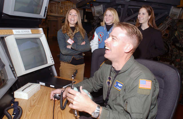City youths from the Albuquerque Youth Leadership Program sponsored by The Greater Albuquerque Chamber of Commerce explore Kirtland Air Force Base (AFB) and the Sandia National Laboratories. US Air Force (USAF) Technical Sergeant (TSGT) Robert Dinsmore, 58th Special Operations Wing (SOW) helicopter instructor, explains the Aero-GUNNER simulator to Rio Rancho junior, Gayle Tripp, left and Sandia High junior, Kristin Colemen and Magan Glennon, right