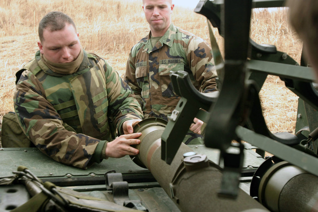 US Marine Corps (USMC) Corporal (CPL) Merchant and Sergeant (SGT) Bivins, Combined Anti-Armor Team, Weapons Company, 2nd Battalion (BN), 6th Marine Regiment, 2nd Marine Division (MAR DIV), prepare a Hughes TOW (Tube-launched, Optically tracked, Wire command link guided missile) heavy anti-tank weapon system onboard an AM General HMMWV (High-Mobility, Multipurpose Wheeled Vehicle) M998 Series Multipurpose Wheeled Vehicle during a live-fire exercise as a part of Fuji Combined Arms Operation FY-04-2