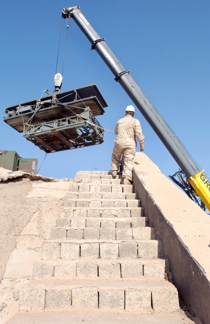 The US Air Force (USAF) 447th Expeditionary Civil Engineer Squadron (ECES) Heavy Equipment Operators use their crain to lower a radar unit for the 447th Expeditionary Air Control Squadron (EACS) at Baghdad International Airport (BIA), Iraq (IRQ), in support of Operation IRAQI FREEDOM