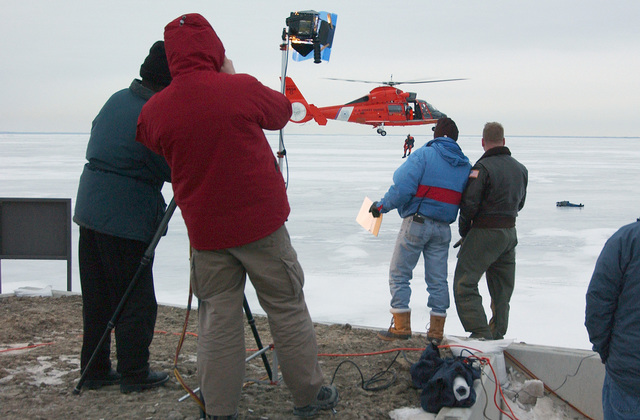 An HH-65A Dolphin chopper from the US Coast Guard Air Station (USCGAS), Detroit, Michigan (MI), approaches a simulated victim lying on frozen Lake St.Clair near Selfridge Air National Guard Base (ANGB), Michigan (MI), while a cameracrew broadcasts the action live on the Channel 7 Action News