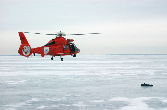 An HH-65A Dolphin chopper from the US Coast Guard Air Station (USCGAS), Detroit, Michigan (MI), approaches a simulated victim lying on frozen Lake St.Clair near Selfridge Air National Guard Base (ANGB), Michigan (MI)