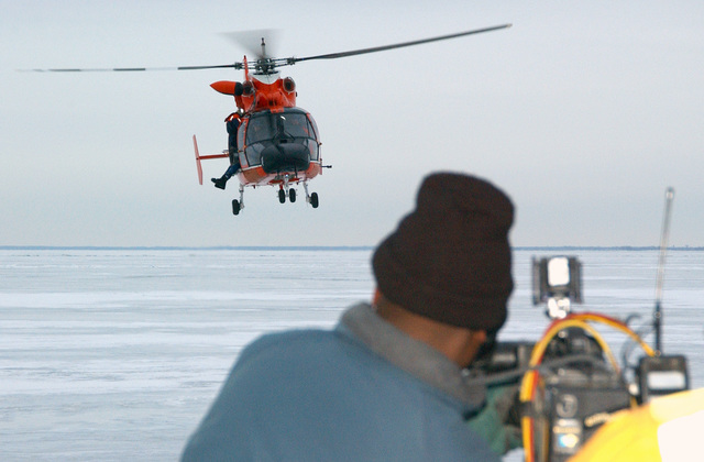 An HH-65A Dolphin chopper from the US Coast Guard Air Station (USCGAS), Detroit, Michigan (MI), rescues a simulated victim from frozen Lake St.Clair near Selfridge Air National Guard Base (ANGB), Michigan (MI), while a cameracrew broadcasts the action live on the Channel 7 Action News