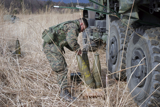US Marine Corps (USMC) Corporal (CPL) Johnathon Huizar, CHIEF, Gun One, Kilo Battery, 3rd Battalion (BN), 10th Marine Regiment, 2nd Marine Division (MAR DIV), prepares M198 155mm Towed Howitzer rounds for a live-fire exercise during a field operation in the North Fuji Training Area as part of Fuji Combined Arms Operation FY-04-2