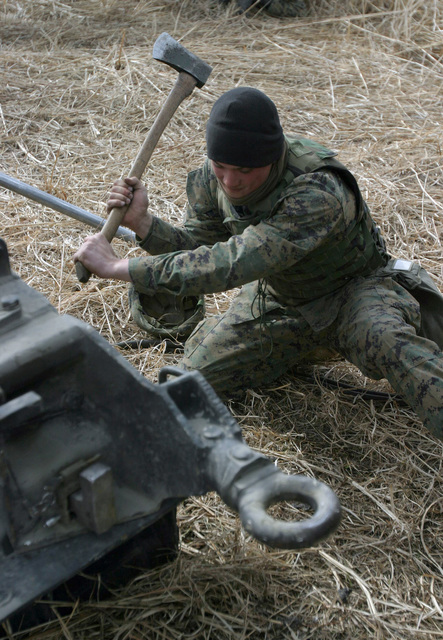 US Marine Corps (USMC) Lance Corporal (LCPL) Alex Fabian, GUNNER, Gun One, Kilo Battery, 3rd Battalion (BN), 10th Marine Regiment, 2nd Marine Division (MAR DIV), digs in the spades of an M198 155mm Towed Howitzer during a field operation in the North Fuji Training Area as part of Fuji Combined Arms Operation FY-04-2