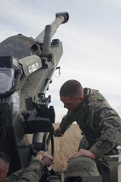 US Marine Corps (USMC) Lance Corporal (LCPL) Alex Fabian, GUNNER, Gun One, Kilo Battery, 3rd Battalion (BN), 10th Marine Regiment, 2nd Marine Division (MAR DIV), raises the tube to maximum elevation on an M198 155mm Towed Howitzer during a field operation in the North Fuji Training Area as part of Fuji Combined Arms Operation FY-04-2