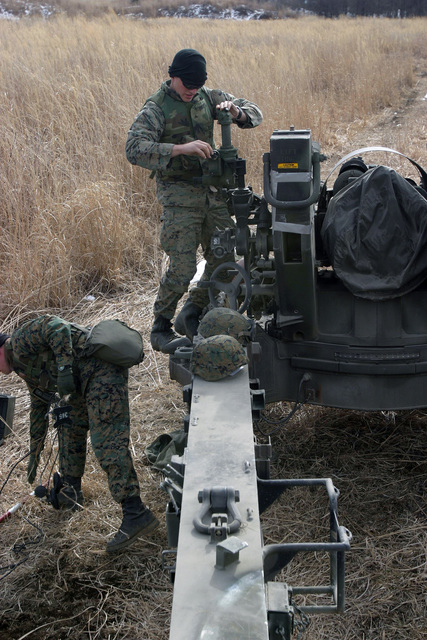 US Marine Corps (USMC) Lance Corporal (LCPL) Joshua Hughes, GUNNER with Gun One, Kilo Battery, 3rd Battalion (BN), 10th Marine Regiment, 2nd Marine Division (MAR DIV), sights in his M198 155mm Towed Howitzer during a field operation in the North Fuji Training Area as part of Fuji Combined Arms Operation FY-04-2