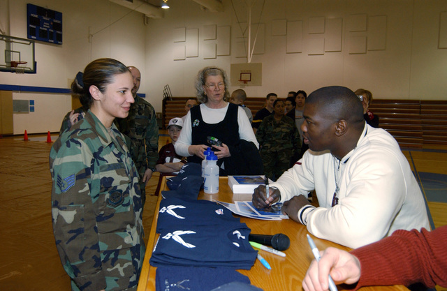 US Air Force (USAF) STAFF Sergeant (SSGT) Jennifer L. Jackson, left, with the 62nd Contracting Squadron (CS), gets an autograph from professional wrestler Shelton Benjamjn from World Wrestling Entertainment (WWE). The WWE athletes were in Tacoma, Washington (WA) to film an upcoming Smack-Down episode at the Tacoma Dome
