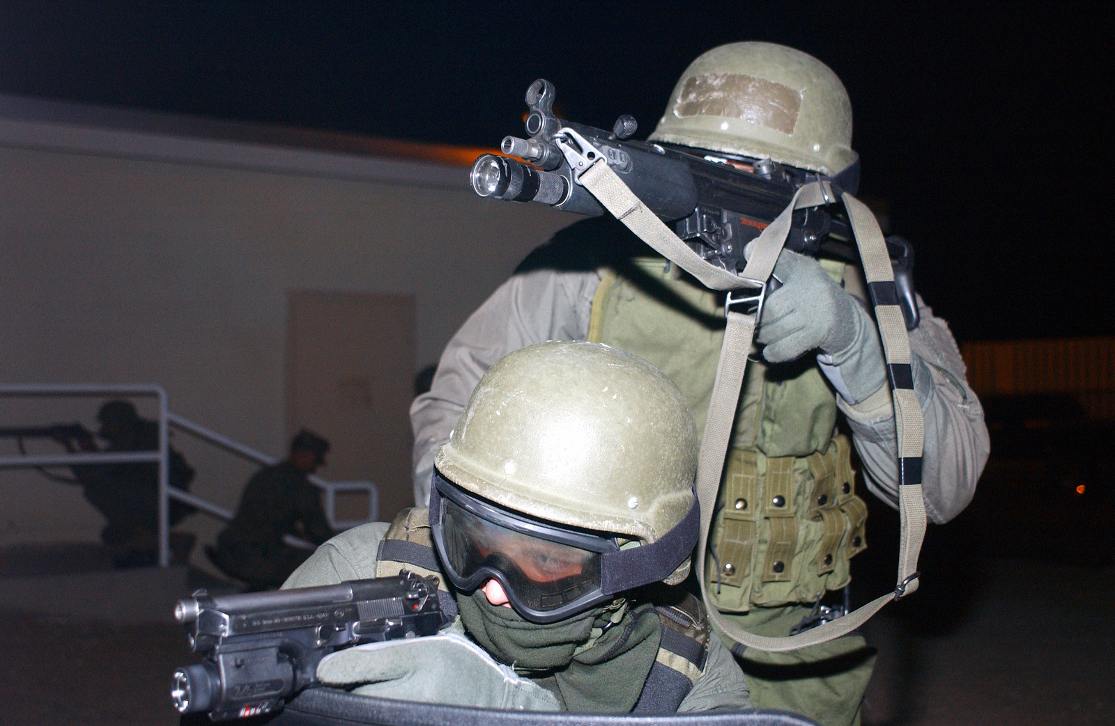 US Navy (USN) Hospital Corpsman Third Class (HM3) Thomas J. Cupo (foreground), is armed with a 9mm handgun, while US Marine Corps (USMC) Corporal (CPL) Stephen L. Clogston, provide cover with a Heclker and Koch 9mm MP5-N sub-machine gun. Both are members of the Marine Special Reaction Team (SRT), participating in a simulated bank robbery scenario at the Marine Air Ground Combat Center in Twentynine Palms, California (CA). The annual training event, conducted by the Provost Marshals Office, is designed to train Military Police and Criminal Investigators proper procedures when dealing with a hostage situation