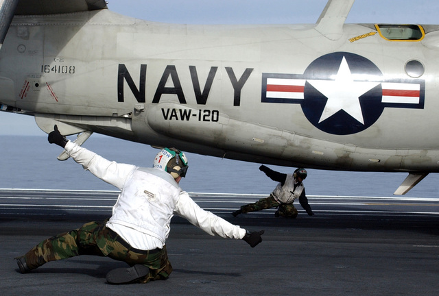Two US Navy (USN) Sailors assigned as Catapult Final Checkers aboard the USN NIMITZ CLASS: Aircraft Carrier, USS JOHN C. STENNIS (CVN 74), give the thumbs up signal before launching a USN E-2C Hawkeye aircraft from Carrier Airborne Early Warning Squadron One Two Zero (VAW-120)