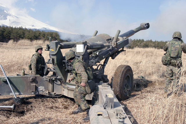 US Marine Corps (USMC) Marine, Kilo Battery, 3rd Battalion (BN), 10th Marine Regiment, 2nd Marine Division (MAR DIV), pulls the lanyard to fire an M198 155mm Towed Howitzer during a field operation in the North Fuji Training Area as part of Fuji Combined Arms Operation FY-04-2