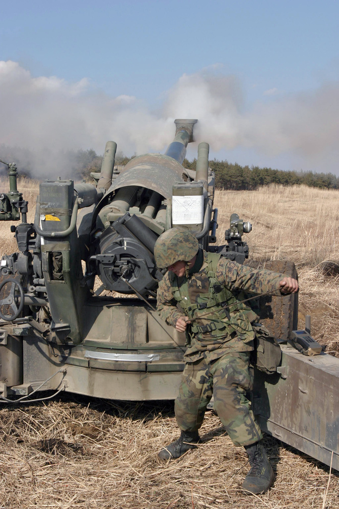 US Marine Corps (USMC) Lance Corporal (LCPL) Al Lambdin, Kilo Battery, 3rd Battalion (BN), 10th Marine Regiment, 2nd Marine Division (MAR DIV), pulls the lanyard to fire an M198 155mm Towed Howitzer during a field operation in the North Fuji Training Area as part of Fuji Combined Arms Operation FY-04-2