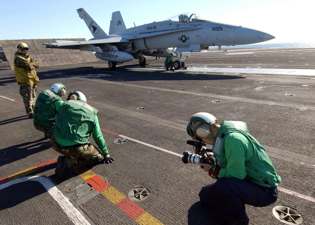 US Navy (USN) Photographer's Mate Third Class (PH3) Christian (foreground) uses a digital video camera to document flight operation aboard the USN Aircraft Carrier USS JOHN F. KENNEDY (CV 67). A USN F/A-18C Hornet aircraft is positioned in the background. CV 67 and Carrier Air Wing One Seven (CVW 17) are taking part in a Composite Training Unit Exercise (COMPTUX)