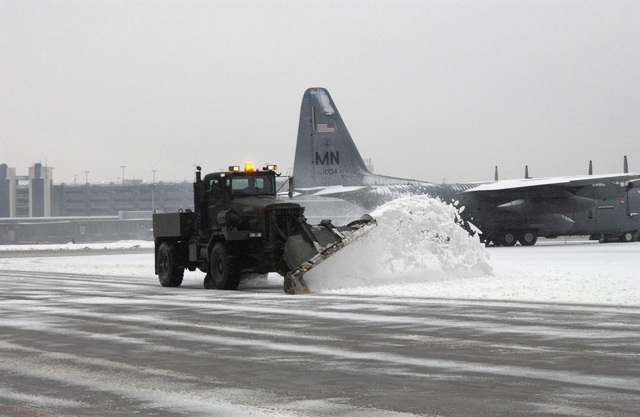 Donald Renstrom, a civilian worker with the Roads and Grounds division of the 133rd Civil Engineering Squadron (CES), Minnisota (MN) Air National Guard (ANG), maneuvers his rollover snow plow carefully around a parked C-130 Hercules cargo aircraft at the Minneapolis, St. Paul International Airport (MSP)