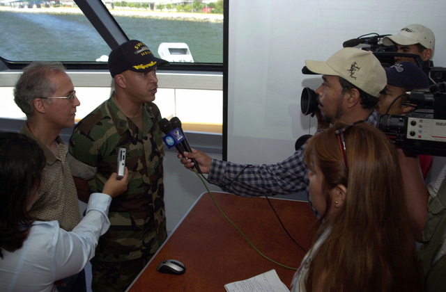 """Members of the Honduran Press interview U.S. Navy CMDR. Clark Price, Jr. (background, left), Commander, High Speed Vessel (HSV) 2""""Swift,""""aboard the vessel at Puerto Cortes, Honduras, on Feb. 24, 2004, in support of New Horizons 04 during the Joint Logistics Over-the-Shore (JLOTS) Exercise.  JLOTS is overseen by the U.S. Transportation Command and consists of the loading and off-loading of ships in the area of underdeveloped ports.  (U.S. Army photo by Kaye Richey) (Released)"""