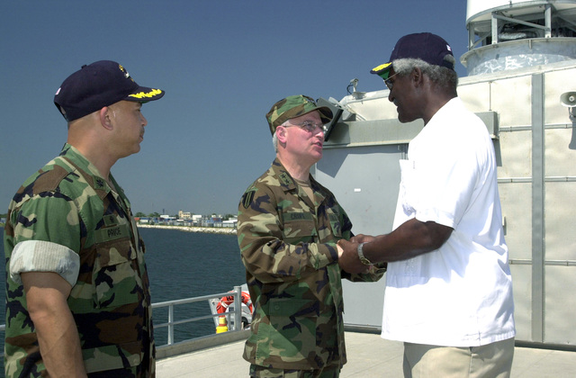 """U.S. Army MAJ. GEN. William Crupe (center), Commander, 143rd Transportation Command, Orlando, Fla., shakes hands with the Honorable Larry Palmer, U.S. Ambassador to Honduras, onboard the High Speed Vessel (HSV) 2""""Swift""""at Puerto Cortes, Honduras, on Feb. 24, 2004, in support of New Horizons 04 during the Joint Logistics Over-the-Shore (JLOTS) Exercise. U.S. Navy CMDR. Clark Price, Jr. (left), Commander, High Speed Vessel (HSV) 2""""Swift,""""is also present in the photograph.  JLOTS is overseen by the U.S. Transportation Command and consists of the loading and off-loading of ships in the area of underdeveloped ports.  (U.S. Army photo by Kaye Richey) (Released)"""
