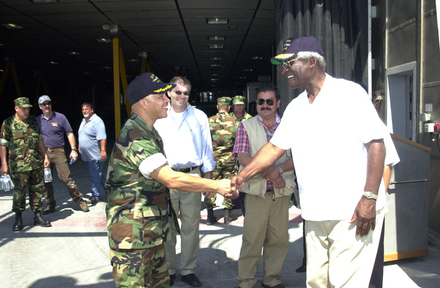 """U.S. Navy CMDR. Clark Price, Jr. (foreground, left), Commander, High Speed Vessel (HSV) 2""""Swift,""""shakes hands with the Honorable Larry Palmer, U.S. Ambassador to Honduras, onboard the High Speed Vessel (HSV) 2""""Swift""""at Puerto Cortes, Honduras, on Feb. 24, 2004, in support of New Horizons 04 during the Joint Logistics Over-the-Shore (JLOTS) Exercise.  JLOTS is overseen by the U.S. Transportation Command and consists of the loading and off-loading of ships in the area of underdeveloped ports.  (U.S. Army photo by Kaye Richey) (Released)"""