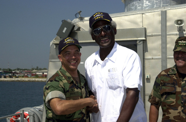 """U.S. Navy CMDR. Clark Price, Jr. (left), Commander, High Speed Vessel (HSV) 2""""Swift,""""shakes hands with the Honorable Larry Palmer, U.S. Ambassador to Honduras, onboard the High Speed Vessel (HSV) 2""""Swift""""at Puerto Cortes, Honduras, on Feb. 24, 2004, in support of New Horizons 04 during the Joint Logistics Over-the-Shore (JLOTS) Exercise.  The Army of Honduras (Ejercito de Honduras-EH) COL. Efraim Ochoa Aviles (right), Commander, 105th Infantry Brigade, is also present in the photograph.  JLOTS is overseen by the U.S. Transportation Command and consists of the loading and off-loading of ships in the area of underdeveloped ports.  (U.S. Army photo by Kaye Richey) (Released)"""