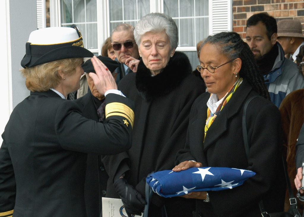 """US Navy (USN) Rear Admiral (lower half) (RDML) Ann E. Rondeau, Commander, Navy Region Midwest/Commander, Naval Service Training Command, salutes the National ENSIGN after presenting it to Sala Marilyn Steinbach, daughter of William Sylvester White, one of the Navys first 13 African-American officers. Dubbed """"The Golden 13"""", he was one of the Navys first 13 African-American officers. Mr. White, 79, served in the Navy from 1943-1946, earning the rank of Lieutenant Junior Grade (LTJG). Following his commission at Naval Training Station, Great Lakes in 1944, he served as a Public Affairs Officer (PAO) at both Ninth Naval District and in Washington, D.C. A 1937 graduate of the University of..."""