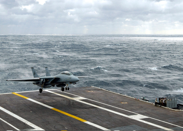 A US Navy (USN) F-14A Tomcat fighter aircraft, Fighter Squadron 213 (VF-213), Blacklions, Naval Air Station (NAS) Oceana, Virginia (VA), comes for a landing on the flight deck of the USN Nimitz Class Aircraft Carrier USS HARRY S. TRUMAN (CVN 75) during rough seas. The TRUMAN is currently undergoing carrier qualifications and flight deck certification off the Atlantic coast