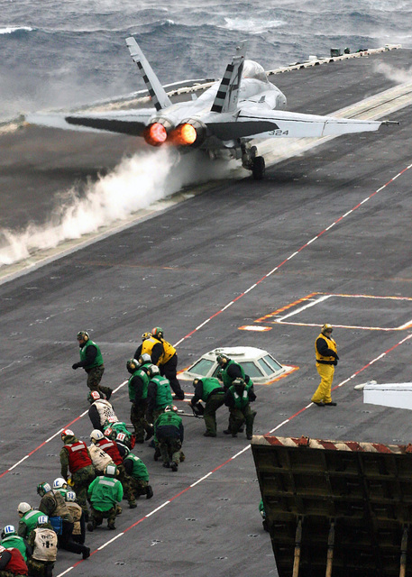 US Navy (USN) Flight deck personnel kneel between the foul lines near the Waist Bubble as a USN FA-18C Hornet fighter aircraft launches from Catapult 2 off the USN Nimitz Class Aircraft Carrier USS HARRY S. TRUMAN (CVN 75). The TRUMAN is currently undergoing carrier qualifications and flight deck certification off the Atlantic coast