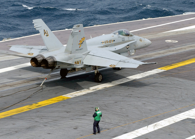 A US Navy (USN) F/A-18C Hornet fighter aircraft, Strike Fighter Squadron 87 (VFA-87), Golden Warriors, Naval Air Station (NAS) Oceana, Virginia (VA), releases the arresting wire after recovering aboard the Nimitz Class Aircraft Carrier USS HARRY S. TRUMAN (CVN 75). The TRUMAN is currently undergoing carrier qualifications and flight deck certification off the Atlantic coast