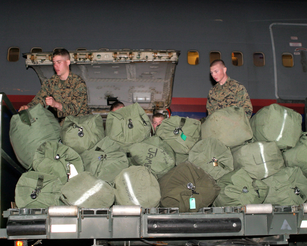 US Marine Corps (USMC) Marines, 3rd Battalion (BN), 8th Marine Regiment, Camp Lejeune, North Carolina (NC), prepare to load personal gear aboard a Boeing 747 at the Aerial Point of Embarkation (APOE), Marine Corps Air Station (MCAS) Cherry Point, NC, prior to flying to Haiti in order to establish a police force element there