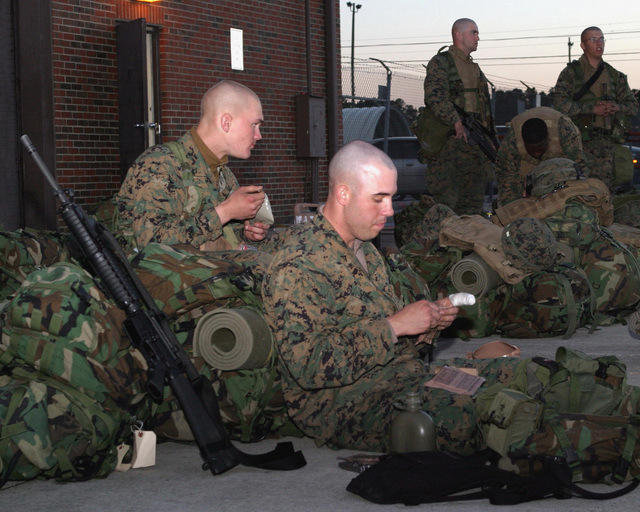 US Marine Corps (USMC) Marines, Lance Corporal (LCPL) Alejandro Conde (front) and Private First Class (PFC) David Terril, both 0311 Rifleman, 3rd Battalion (BN), 8th Marine Regiment, Camp Lejeune, North Carolina (NC), eat their evening meal while waiting at the Aerial Point of Embarkation (APOE), Marine Corps Air Station (MCAS) Cherry Point, NC, to fly to Haiti in order to establish a police force element there