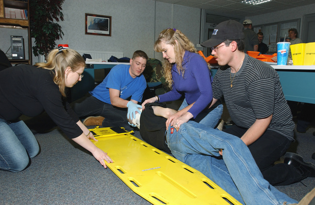 US Air Force (USAF) personnel (left to right) Allison Willits, Jeremy Rath, Debra Lockwood, and Lloyd Willits, Royal Air Force (RAF) Mildenhall, England (ENG), practice immobilizing an injured patient as part of the Emergency Medical Technician (EMT) course they are taking at RAF Mildenhall through Central Texas College