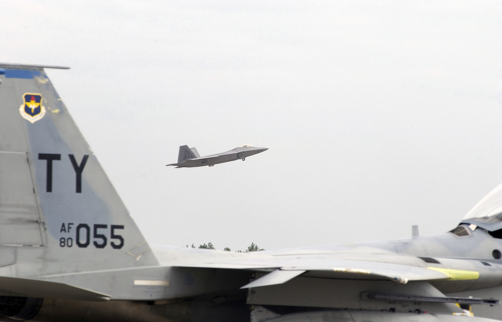 A US Air Force (USAF) 43rd Fighter Squadron (FS) F/A-22 Raptor Advanced Tactical Fighter (ATF) makes a low pass before landing at Tyndall Air Force Base (AFB), Florida (FL), while in the foreground sits a parked 95th FS F-15 Eagle fighter aircraft