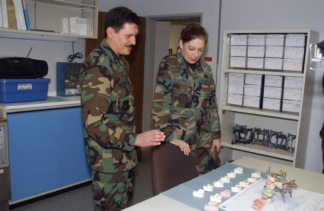 US Air Force (USAF) Brigadier General (BGEN) Rosanne Bailey (center), Commander, 435th Air Base Wing (ABW), Ramstein Air Base (AB), and Commander, Kaiserlautern Military Community (KMC), Germany (DEU), looks at dental molds along with Lieutenant Colonel (LTC) Joe Villalobos, Commander, 435th Dental Squadron (DS), during her mission review visit to the Sembach Annex, KMC, Germany
