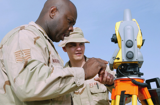 US Air Force (USAF) Technical Sergeant (TSGT) Jimmy Warner (left) and AIRMAN First Class (A1C) Julian Miranda, 332nd Civil Engineer Squadron (CES), inspect a theodolite laser range finder (transit machine) they are using to sight tent floors for the correct alignment at Silver City to set up extra tents to accommodate the continuous flow of USAF personnel reporting for temporary duty (TDY) assignment at Balad Air Base (AB), Iraq (IRQ), during Operation IRAQI FREEDOM