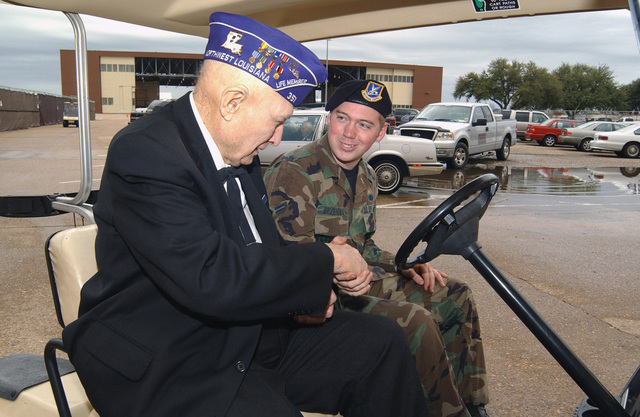 US Air Force (USAF) AIRMAN First Class (A1C) Michael Brizendine (right), 2nd Security Forces Squadron (SFS), Barksdale Air Force Base (AFB), Louisiana (LA), shakes hands with 91-year old Lieutenant Colonel (LTC) John Livingston (USAF retired) prior to escorting him into the Barksdale Retiree Activities Offices annual Purple Heart Luncheon. LTC Livingston is the oldest of the 179 Purple Heart recipients to be honored at the luncheon