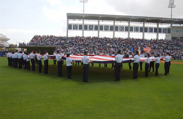 US Air Force (USAF) personnel from MacDill Air Force Base (AFB), Florida (FL), present a large American Flag during the playing of the National Anthem at Legends Field in Tampa, Florida (FL), on the opening day of Spring Training for the New York Yankees, who are about to play the Philadelphia Phillies