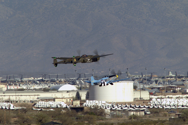 Two World War II (WW II) era aircraft, a P-38J Lightning pursuit (fighter) aircraft and a P-51 Mustang pursuit (fighter) aircraft, take off in formation, with the Aerospace Maintenance and Regeneration Center (AMARC) seen in the background, during the Heritage Conference being held at Davis-Montham Air Force Base (AFB), Arizona (AZ)