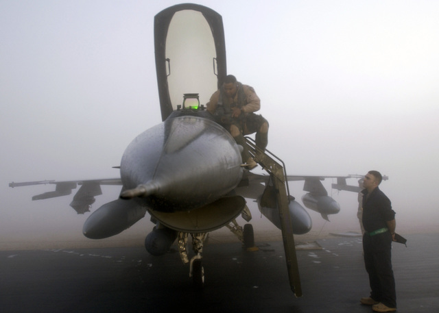 US Air Force (USAF) Captain (CPT) Ronnie Hawkins (left), 510th Expeditionary Fighter Squadron (EFS), Baghdad Buzzards Border patrol, Aviano Air Base (AB), Italy (ITL), prepares to board his F-16 Fighting Falcon (also referred to as a Viper by many USAF pilots because that was the original General Dynamics project name) fighter aircraft, while a ground crew member stands at-ease, prior to leaving his deployed location and flying back to Aviano AB