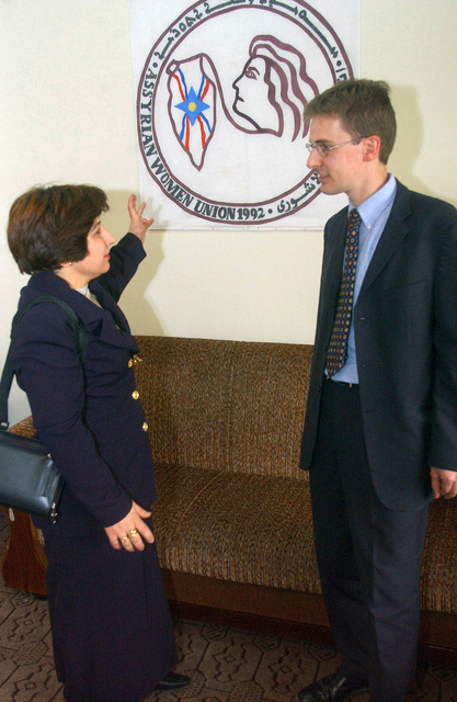Sofia Suheil (left), a founder of the Assyrian Womens Union (AWU) Building, explains the AWU crest that is on display to Mr. Andrew Allen, British Public Affairs Officer, during the grand opening celebration of the AWU Building