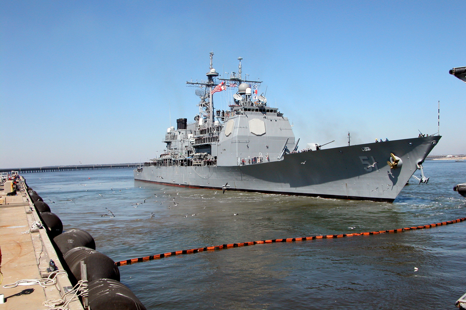 A starboard bow view of the US Navy (USN) TICONDEROGA CLASS: Guided Missile Cruiser (Aegis), USS THOMAS S. GATES (CG 51) being assisted by a commercial tugboat, as the ship gets underway from its homeport at Naval Station Pascagoula, Mississippi (MS)