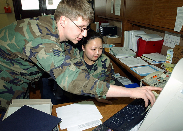 US Air Force (USAF) STAFF Sergeant (SSGT) Jeffrey Quade (left), Unit Training Manager, 35th Communications Squadron (CS), Misawa Air Base (AB), Tohoku Region, Japan (JPN), explains a Microsoft Excel application to AIRMAN First Class (A1C) Gina McGowan