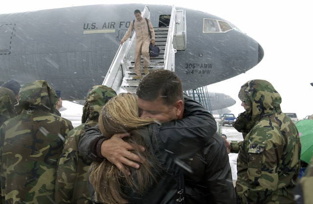 US Air Force (USAF) Lieutenant Colonel (LTC) Kenneth Keslar, 32nd Air Refueling Squadron, is embraced by wife Donna, after disembarking from a USAF KC-10 Extender aircraft amid a snowstorm, at McGuire Air Force Base (AFB), New Jersey (NJ). LCT Keslar and members of his Unit are returning home from a 60-day deployment, in support of Operation IRAQI FREEDOM
