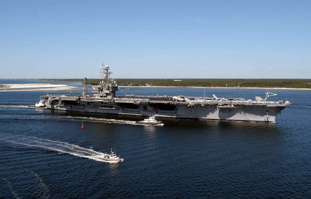 An aerial starboard side view of the US Navy (USN) Aircraft Carrier, USS JOHN F. KENNEDY (CV 67), underway being escorted by a commercial tugboat, and a harbor patrol craft as the ship enters the harbor at Naval Air Station Pensacola, Florida (FL), for a four-day port visit following the completion of a Composite Training Unit Exercise (COMTUEX) in the Gulf of Mexico. COMPTUEX is an intermediate level exercise designed to forge the strike group into a cohesive fighting team and is a critical step in pre-deployment training