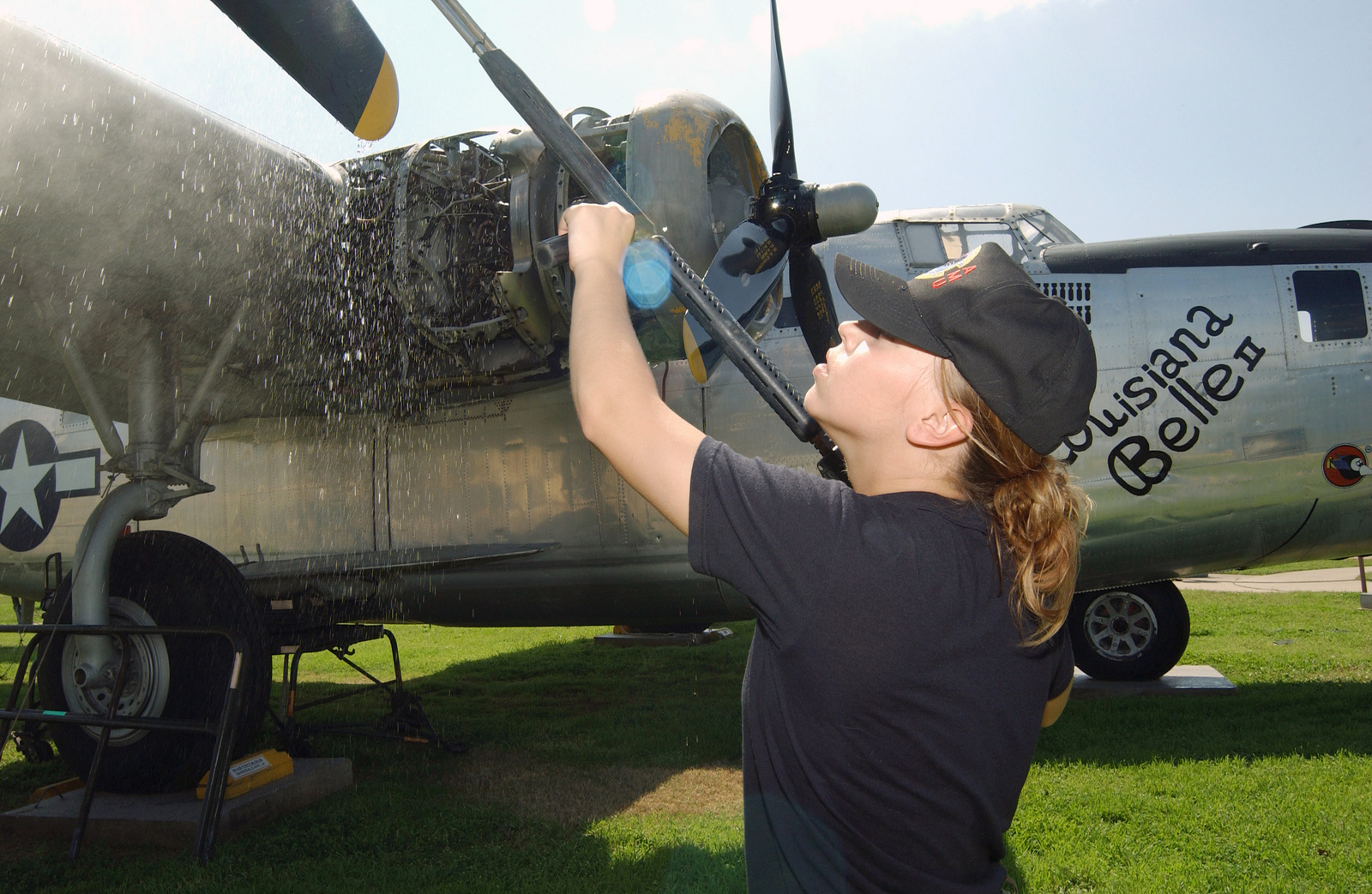 US Air Force (USAF) AIRMAN First Class (A1C) Kelli England (left), 2nd Civil Engineer Squadron (CES) cleans a propeller on a mock up World War Two (WII) B-24J as part of a team assigned to clean up the Barksdales Material Heritage on Display at the 8th Air Force Museum, located at Barksdale Air Force Base (AFB), Louisiana (LA)