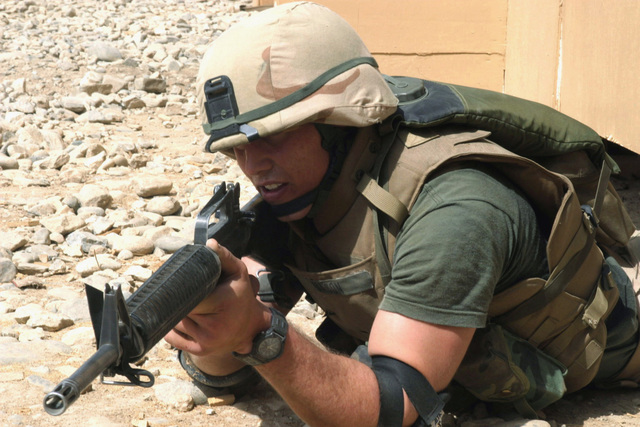 US Marine Corps (USMC) Lance Corporal (LCPL) Justin M. Layman, Headquarters Company (HQ Co), 6th Marine Regiment, 2nd Marine Division (MARDIV), provides cover as he practices a squad rush drill while conducting a daytime Quick Reaction Force (QRF) training exercise at Bagram Air Base (AB), Parvan Province, Afghanistan (AFG), during Operation ENDURING FREEDOM. LCPL Layman has participated in both daytime and nighttime QRF training in case he is needed to support perimeter security