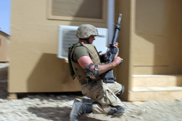 US Marine Corps (USMC) Lance Corporal (LCPL) Justin M. Layman, Headquarters Company (HQ Co), 6th Marine Regiment, 2nd Marine Division (MARDIV), practices a squad rush drill while conducting a daytime Quick Reaction Force (QRF) training exercise at Bagram Air Base (AB), Parvan Province, Afghanistan (AFG), during Operation ENDURING FREEDOM. LCPL Layman has participated in both daytime and nighttime QRF training in case he is needed to support perimeter security